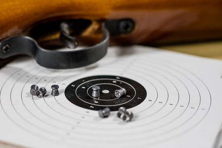 Shooting accessories on a wooden table in a shooting range. Shield and projectiles for pneumatic weapons before shooting. Black background.