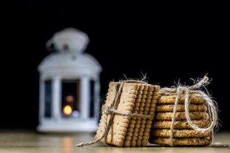 Cookies tied with a gray jute string into a bow. Cookies of sweets on a wooden kitchen table. Black background.
