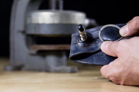 Repairing a bicycle tube in a tire bonding workshop. Detek repair station in the vulcanization workshop. Black background.
