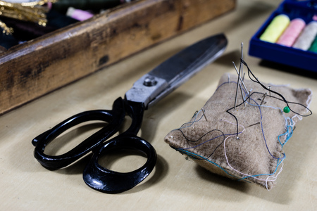 Garment accessories spread on a light wooden table. Threads, scissors and sewing needles in a tailoring workshop. Sewing station.