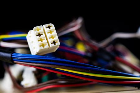 Cables eléctricos, enchufes y conectores en una mesa de taller de madera. Accesorios y componentes eléctricos. Fondo negro.