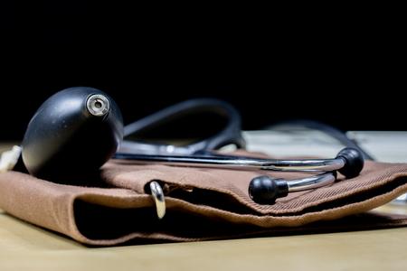 Medizinisches Zubehör auf einem Holztisch. Stethoskop und ein medizinisches Blutdruckmessgerät in der Arztpraxis. Eine medizinische Zeitschrift.
