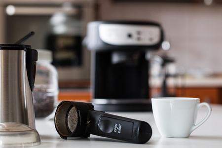 Morning coffee in the kitchen. Coffee grinder and coffee maker with coffee makers on a white kitchen table. Time of the day, morning. Stockfoto