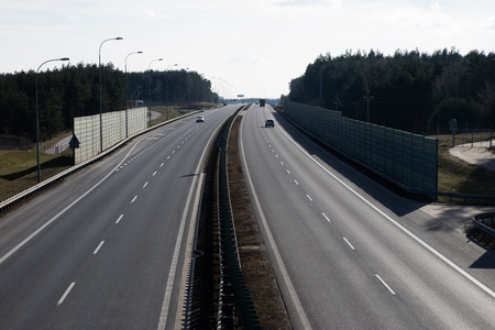 The high-speed road seen from the viaduct. Two-lane road and cars on the way. Season of the spring.
