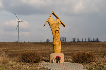 Wooden chapel standing near the road, Europe. A shrine with a wind turbine in the background. Season of the spring.