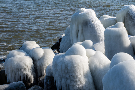 Baltic Sea in Poland. Entrance to the port, ice-covered concrete breakwater. Season winter.