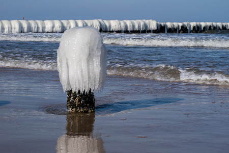Baltic Sea in Poland. Sea shore and falachron with icy wooden pegs. Season winter. Stock fotó