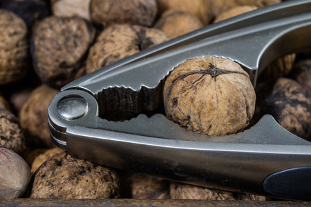 Walnuts on a wooden kitchen table. Nuts and a black wooden crate with a nutcracker. Black background.