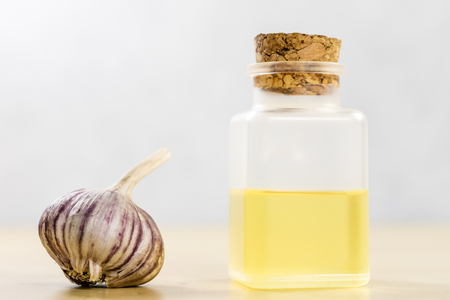 The specificity of garlic for flu. Healing juice in a vial on a wooden table. White background.