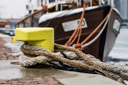 A mooring bollard entwined with a mooring rope. Moored ships at the port quay. Season winter.