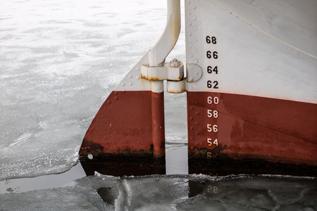 The rudder blade of a large ship in the port. Passenger ship moored in the port. Season winter.