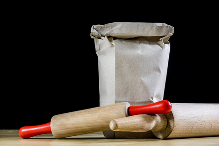 Flour and rolling pin for kneading the dough on the kitchen table. Accessories and kitchen products. Black table top.
