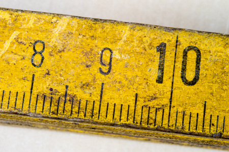 Old measure carpentry on a wooden workshop table. Joinery accessories shown in a large magnification. Light background.