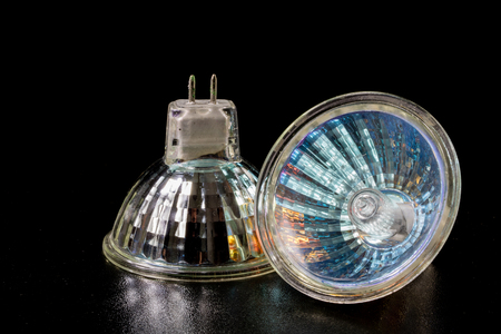 Halogen bulb in a reflective shade. Lighting accessories on a dark tole. Black background.