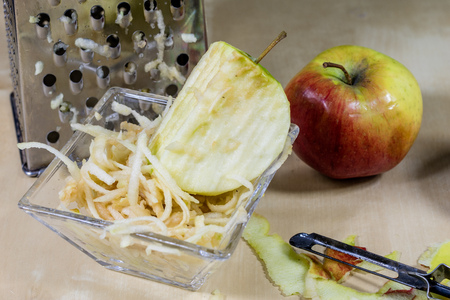 The apple grated on a kitchen grater. Kitchen countertop and preparation of salads. Dark background.