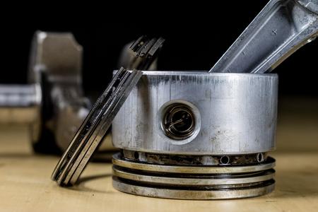 Wał korbowy, tłok i inne części silnika spalinowego. Zdemontowany jednotłokowy czterosuwowy silnik na stole warsztatowym. Czarne tło.