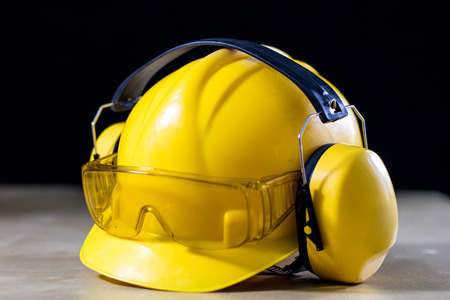 Protective clothing and tools lying on the workshop table. Buy and helmet for a construction worker. Black background. Stock Photo