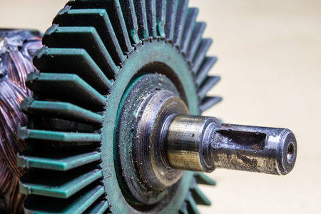 Old worn out gears in an angular gear. Mechanical accessories designed for regeneration in a repair shop. Black background.