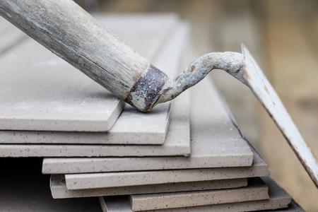 Tegels leggen en snijden. Gereedschappen en bouwmaterialen op een werkpositie. Tegels voor industriële en technische toepassingen. Materiaal Gres. Stockfoto
