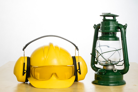 Protective helmet and oil lamp on a wooden table. Safety and health protection accessories for construction workers. White isolated background. Reklamní fotografie