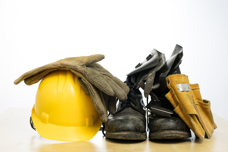 Protective helmet and work boots on a wooden table. Safety and health protection accessories for construction workers. White isolated background. Stockfoto
