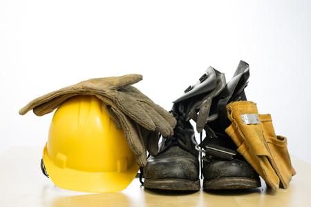 Kask ochronny i buty robocze na drewnianym stole. Akcesoria BHP dla pracowników budowlanych. Białe tło na białym tle.