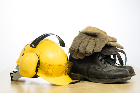 Protective helmet and work boots on a wooden table. Safety and health protection accessories for construction workers. White isolated background. Archivio Fotografico