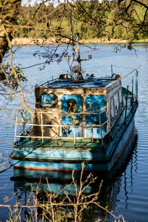 A fishing boat moored to the shore of the lake. Old fishermens boat prepared for fishing on lakes. Season of the spring.