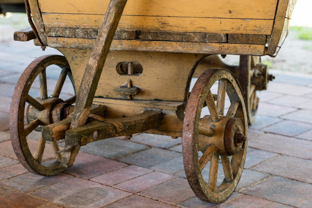 Old wooden wheels for horse cart. Open-air museum where various types of cars and wheels are shown. Season of the spring.