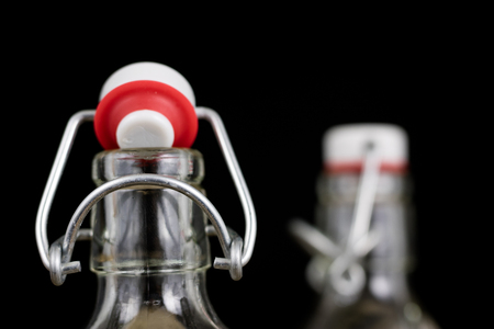 Universal closure of a beverage bottle. Airtight cap closing transparent glass container. Dark background.