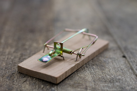 Mousetrap on an old wooden table. Metal accessories for extermination of small rodents. Dark background. 免版税图像 - 103861087