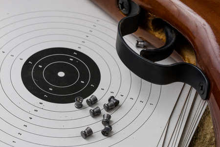 Shooting and pneumatic weapon. Shield and hits with lead bullets on a wooden table. Dark background.