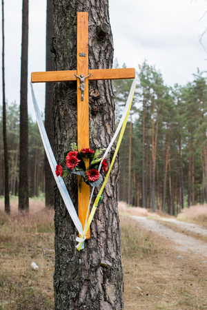 Holy cross at a dirt road in the forest. A forested sandy path leading through a pine forest. Season of the summer.