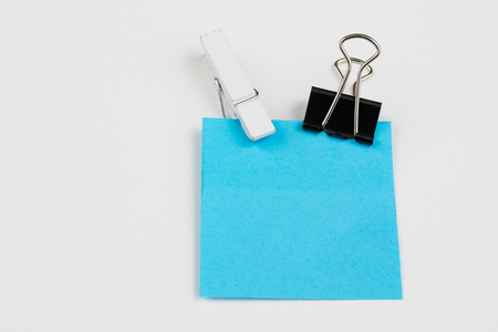Blank colored sticky notes with clips. Office accessories for listing and memorizing on the table. White background.