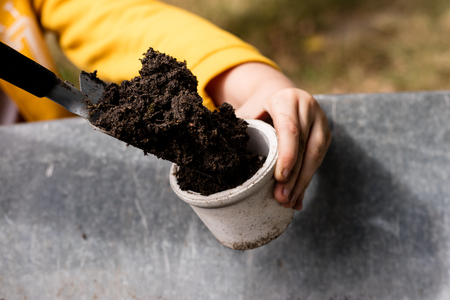 Black soil and flower pots intended for flower growing. Transplanting plants in a home garden. Season of the summer. Stock Photo