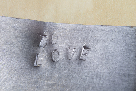 Stamped TO LOVE inscription in metal. The inscription on metal plates. Place - locksmith's workshop. Standard-Bild - 104317608