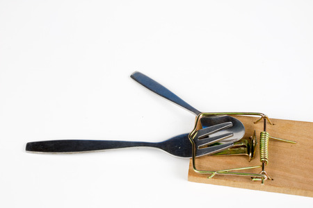 Cutlery and mousetrap on a white table. Fork and spoon caught in a trap. White background.