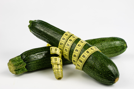 Zucchini on a white table. Tailor measure to measure the waist circumference during the diet. Light background.
