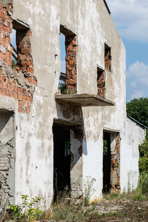 Destroyed state farm in Central Europe. Ruins of farm buildings. Season of the summer.
