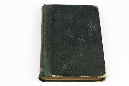 Old destroyed book on a white table. Old-style cover. White isolated background.