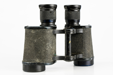 Old metal binoculars on a white table. Old military accessories for infantry. White background.