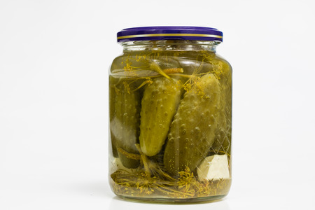 Vegetables in jars prepared for the winter. Tasty preserves on a white kitchen table. White background.