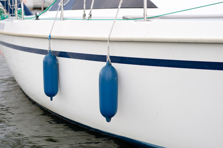 Bumpers hung at the side of the yacht. Moored and secured boats at the pier over the lake. Season of the summer. Stock Photo