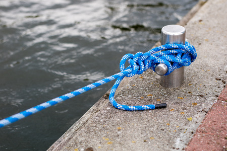 Bollard with a mooring line wrapped around it. Moored boats at the yacht harbor. Season of the summer. Фото со стока