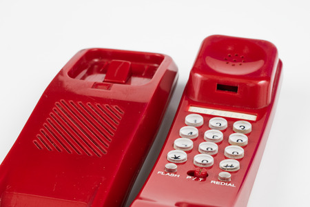 Old red phone with a handset. A telephone set from the nineties. White background.