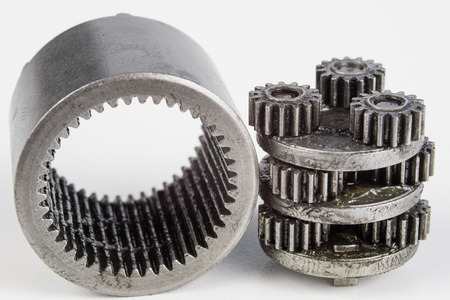 Planetary gear from a small device on a bright table. Gear wheels from a specialist device. White background. Stock Photo