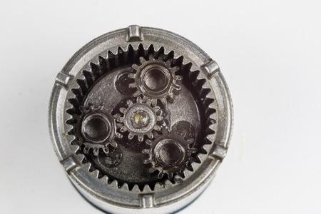 Engranaje planetario de un pequeño dispositivo en una mesa brillante. Ruedas dentadas de un dispositivo especializado. Fondo blanco. Foto de archivo