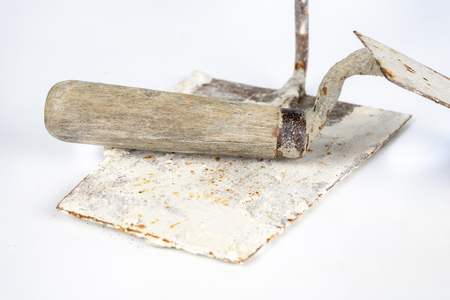 A dirty trowel on a white table. Tools for masons and construction workers. White background.
