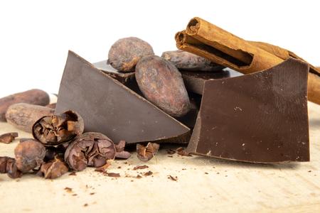 Leckere dunkle Schokolade und Kakaobohnen auf einem weißen Tisch. Süßigkeiten für die Zubereitung von Desserts in der Küche. Weißer Hintergrund.