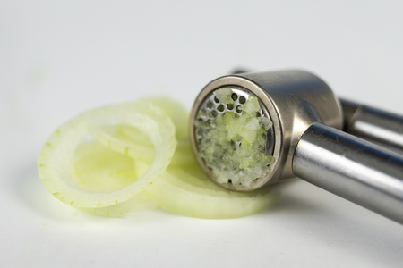 Press to squeeze the onion juice on the kitchen table. Healthy cold juice. White background. Reklamní fotografie